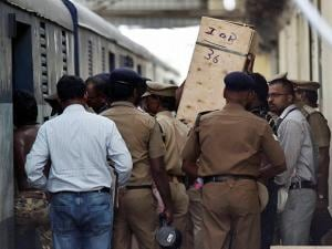 Police recovering one of the four boxes after miscreants broke open the roof of a train