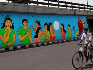 A cyclist passes by a mural painted by a group of deaf persons including two Americans