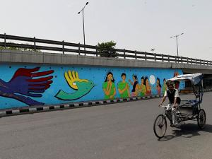 A rickshaw moves past a mural painted by a group of deaf persons