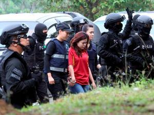 Indonesian suspect Siti Aisyah is escorted by police officers as she arrives at Sepang court