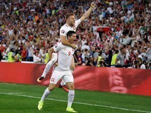 Poland's Robert Lewandowski celebrates with Poland's Jakub Blaszczykowski, top, after scoring the opening goal