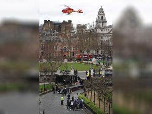 An Air Ambulance comes in to land as emergency services attend to injured persons outside the Houses of Parliament, London