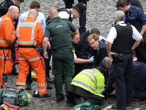 Conservative Member of Parliament Tobias Ellwood, centre, helps emergency services attend to an injured person outside the Houses of Parliament, London