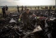 A man looks for the remains of victims in the debris at the crash site