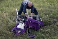 An emergency worker cuts through aircraft seat belts to free the body of a victim at the crash site
