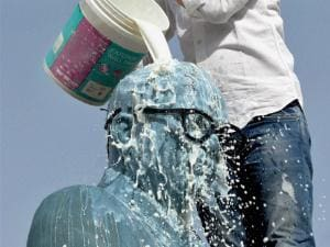A BJYM member cleans a statue of Bhimrao Ambedkar with milk on the eve of his birth anniversary in Bikaner.