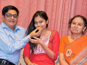 Artika shukla who got the forth rank in the Civil Services Exams 2015, is offered sweets by her parents at their residence in Varanasi