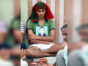 Son of Subedar Karnail Singh holding the photograph of his father during his funeral