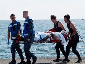 an injured USS Fitzgerald personnel is carried by U.S. military personnel