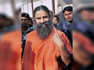 Yoga guru Baba Ramdev showing inked finger after casting his vote during the Uttarakhand assembly poll in Haridwar