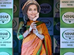 Bollywood actress Vidya Balan covers her face with a mask, during a promotional event in Kolkata