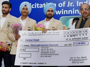 Vijay Goel presents a cheque to Indian Junior hockey team captain Harjeet Singh