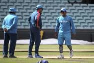 India's cricket captain MS Dhoni, right, smiles after looking at the wicket as his team arrives to train for their Cricket World Cup semifinal match in Sydney