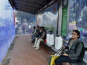 Commuters sitting at Safdarjung Hospital DTC bus stop where Vodafone installed air purifiers to decrease air pollution in New Delhi