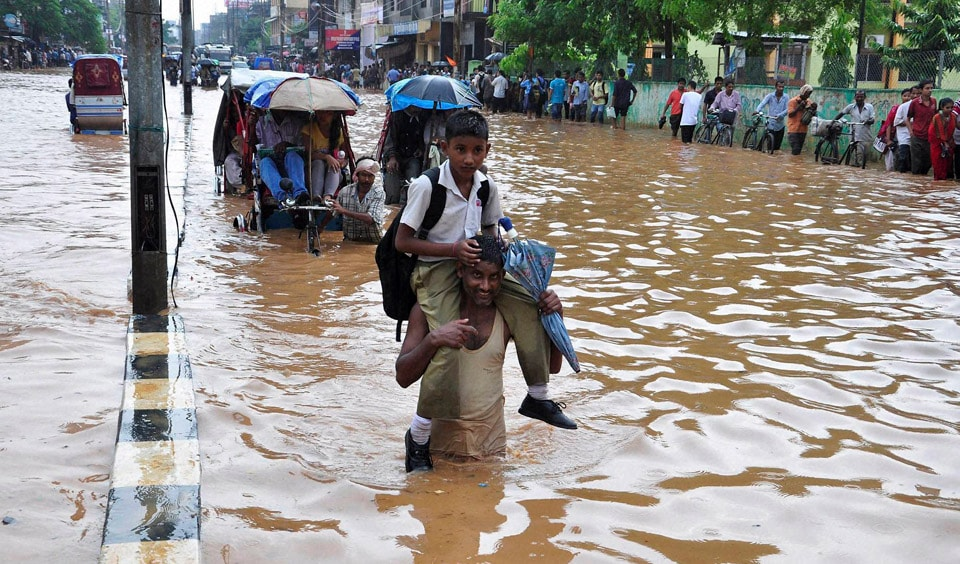 man, carries, child, wades, through, waterlogged road, heavy, downpour, Chandmari