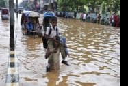 A man carries his child, wades through a waterlogged road after a heavy downpour at Chandmari