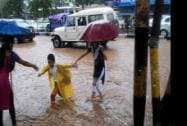 Parents with their children wade through a  waterlogged GS Road after heavy showers