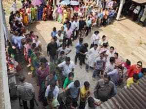 Voters stand in a queue to cast their votes at a polling station during the state assembly elections at Beltola in Guwahati.