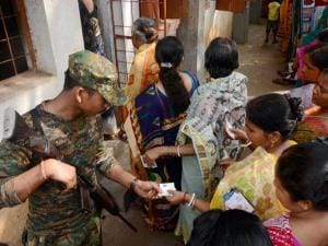 A Central Force jawan checks voter identity cards at a polling booth during the 1st phase West Bengal Assembly Elections in West Medinipur