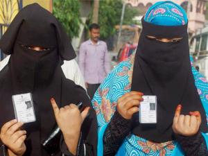 Muslim women show their voter identity cards and marked fingers after casting vote at a polling booth at Bankura in first phace Election