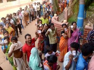 People show their voter cards at a polling booth during the 1st phase West Bengal Assembly Elections in West Medinipur .