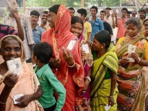 People stand in a queue show their voter cards at a polling booth during the 1st phase West Bengal Assembly Elections in West Medinipur.