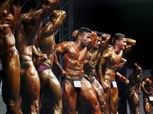 Participants at a state-level body building championship flex their muscles in Thane