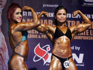 Women participants at a state-level body building championship flex their muscles in Thane