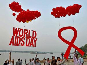 People take part in an AIDS awareness campaign on the bank of river Ganga on the eve of World AIDS day in Kolkata