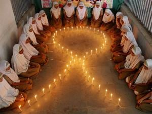 School students lights candles to make AIDS symbol on the eve of World AIDS Day in Ahmedabad