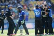 England's Moeen Ali, centre, walks from the field as  New Zealand players celebrate