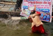 Rajendra Kumar Tiwari participates with cricket fans during a ritual in river Ganga to wish good luck to Team India