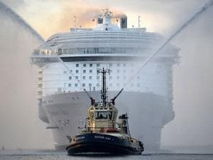 A tug boat leads the way for the world's largest passenger ship, Harmony of the Seas, owned by Royal Caribbean, as it makes her way up Southampton Water, into Southampton, England