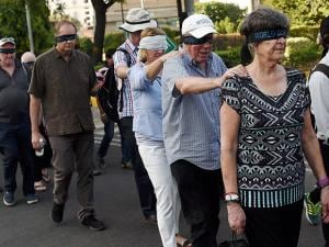 Foreigners taking part in a 'blind walk' at an event organised to mark World Sight Day
