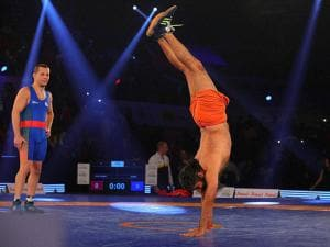 Yoga guru Baba Ramdev displayed his wrestling skills as Olympic medalist Andrey Stadnik looks on during friendly wrestling