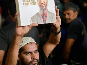 A man holds the book of Islamic preacher Zakir Naik at his video conference in Mumbai