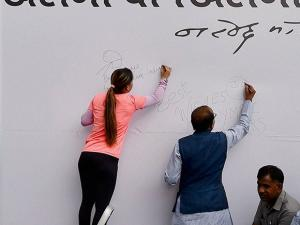 Vijay Goel and Boxer Mary Kom signing the 'Wall Of Wishes'