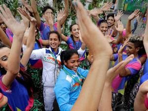 Indian field hockey players Deepika Deepika, center and Preety Dubey dance with performers