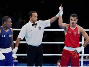 The referee lifts the hand of India's Vikas Krishan to announce him the winner over  Charles Albert Shone Conwell of USA