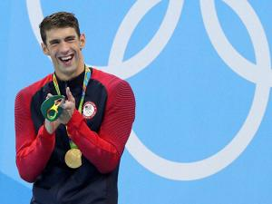 Michael Phelps celebrates with his gold medal after the men's 200-meter butterfly