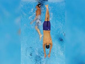 Michael Phelps dives in the pool over teammate Ryan Lochte in the 4 x 200m freestyle relay