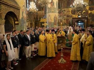 Russia's national Olympic team members listen to Russian Orthodox Church Patriarch Krill