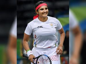 Sania Mirza plays a shot  against  S. Stosur and J. Peers of Australia