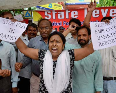 Women employee holds placards against banking sector reforms