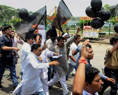 Congress activists carry black balloons and flags