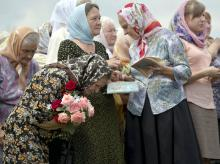 A woman bows during a religious service by villagers in memory of the victims at the crash site of Malaysia Airlines Flight MH17, near the village of Hrabove, eastern Ukraine, on July 22, 2014. A team of Malaysian investigators visited the site along