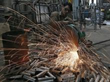 A worker cuts a metal pipe inside a steel furniture production factory in Ahmedabad