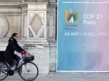A woman cycles past a poster for the COP21 World Climate Summit, in front of Paris hall city, France