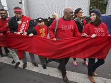 Climate activists carry a red banner during a demonstration at the COP21, United Nations Climate Change Conference, in Le Bourget, north of Paris