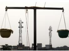 Telecommunication towers are pictured through hanging flower pots at a residential building in Kolkata (Photo: Reuters)